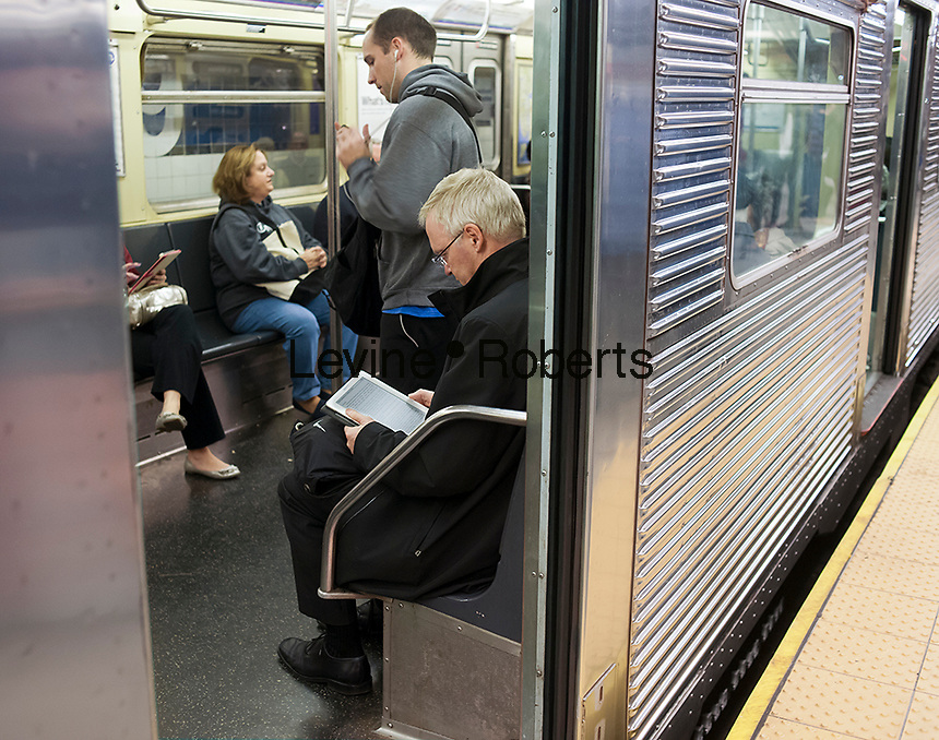 A reader with his Amazon Kindle electronic book ereader in the subway in New York on Thursday, October 11, 2012. (© Richard B. Levine)