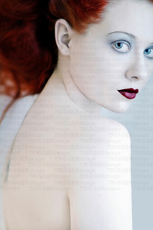 A close up of a girl with red hair and pale skin.