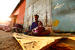 A mother and her child in the loading dock of Port Vila, Vanuatu..Port Vila is the capital and largest city of Vanuatu. Situated on the south coast of the island of Efate, in Shefa Province.Port Vila is the economic and commercial centre of Vanuatu .The population is around 38,000; predominately Melanesian, with small Polynesian, Asian, Australian and European populations, namely French and British..Bislama is spoken by everyone as the day-to-day language. In addition, English and French are also widespread. Other Indigenous languages are also spoken in the city.
