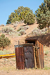 Wooden outhouse with rusting corrugated wind screen