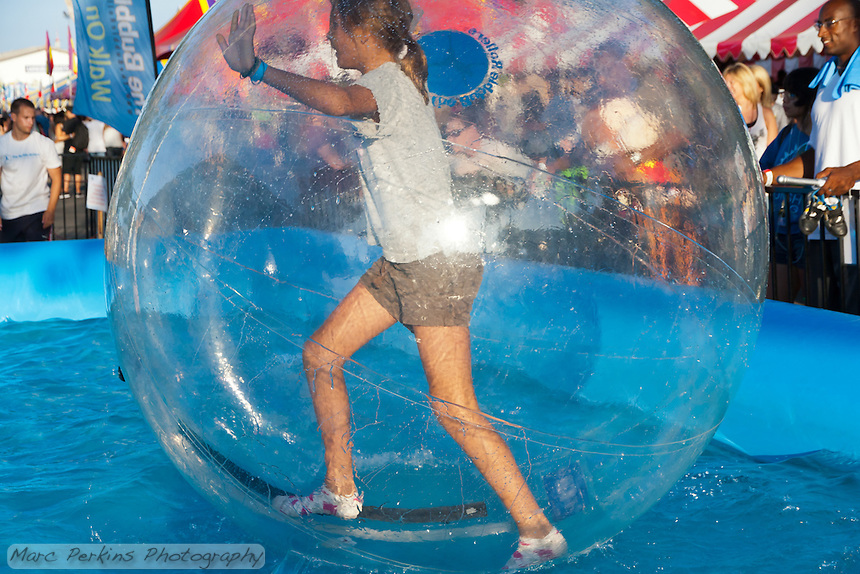 A girl inside an inflated water walking ball manages to stand upright on the water in an inflatable pool at the 2011 Orange County Fair.  In the time I watched the water walking, she was the only person able to actually stand up for any length of time.  And, if you look at the next pictures, she didn't stand for long.  The girl is inside an inflated ball, which allows her to walk on the water, much like a hamster ball.   The Bubble Rollers (http://thebubblerollers.com/) was running this event.   Note: there are serious safety concerns with some types of water ball use: http://consumerist.com/2011/03/cpsc-deems-water-walking-balls-a-deadly-danger.html