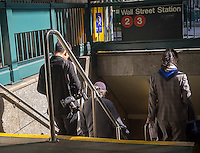 Travelers enter a Wall Street subway entrance in New York on Sunday, October 16, 2016. (©Richard B. Levine)