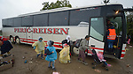 Refugees get off a bus in the rain and prepare to cross the border into Croatia near the Serbian village of Berkasovo. Hundreds of thousands of refugees and migrants from Syria, Iraq and other countries--including many children--have flowed through Serbia in 2015, on their way to western Europe.