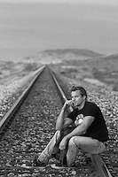 man in deep thought while sitting on railroad tracks in New Mexico