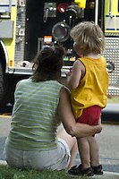 Mother and daughter watch Fire truck at parade.
