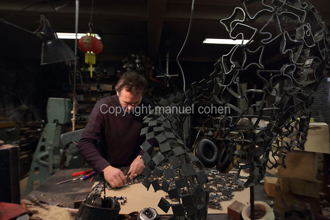 Nicolas Desbons, metalworker and artist, selecting steel pieces for a sculpture made from cross-sections of steel tubes manipulated into organic profiles and soldered together, and a sculpture in the foreground, in his Soleil Rouge workshop, photographed in 2017, in Montreuil, a suburb of Paris, France. Desbons works mainly in steel but often in conjunction with other materials such as fibreglass, glass and clay, using both cold metal and forge techniques. He produces both figurative and abstract sculptures as well as furniture and lighting. Picture by Manuel Cohen