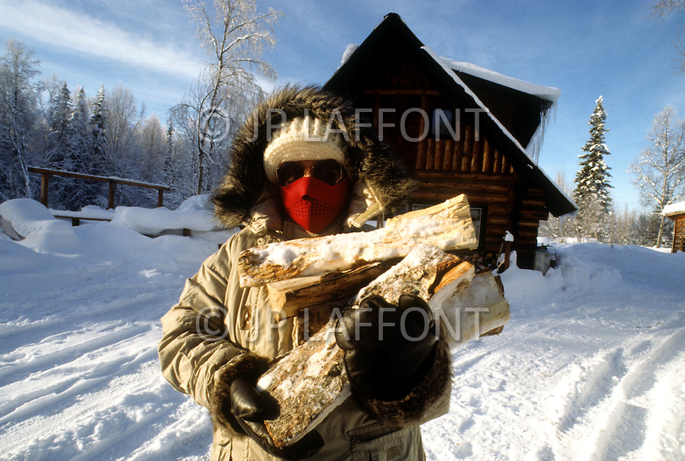 Talkeetna, Alaska, U.S.A, January 1989. A sudden cold wave struck Alaska resulting to the temperature falling under 50 degrees Centigrade (58 degrees Fahrenheit). Clara Wallace, 55, carrying frozen log to her house.