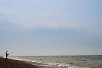 Man fishing on Cley Beach, Norfolk, United Kingdom