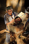 Man grinds coffee fruits to release the bean.