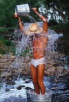 Man standing in a stream in his underwear while pouring water over himself in New Mexico