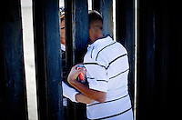San Diego, Oct. 20, 2007 - Husband, Gustavo Sanchez reaches through the border fence at Border State Park to his wife, Vanessa, who is on the Tijuana side. The couple have been married for just over a year. They are separarted by the border: he is a U. S. citizen and she a Mexican citizen. Their access to one another is limited, as she cannot get a visa and he is on parole. The couple meets here on the weekends as it offers the only place the couple can touch one another.
