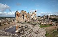 The colonnaded facade which lined the Forum or marketplace and forms one side of the Roman Basilica, 217 AD, used as courts of justice and city governance, seen from the Capitoline Temple, with its altar in the foreground, Volubilis, Northern Morocco. Volubilis was founded in the 3rd century BC by the Phoenicians and was a Roman settlement from the 1st century AD. Volubilis was a thriving Roman olive growing town until 280 AD and was settled until the 11th century. The buildings were largely destroyed by an earthquake in the 18th century and have since been excavated and partly restored. Volubilis was listed as a UNESCO World Heritage Site in 1997. Picture by Manuel Cohen