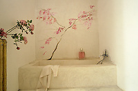A cherry tree has been painted on the wall of the simple bathroom