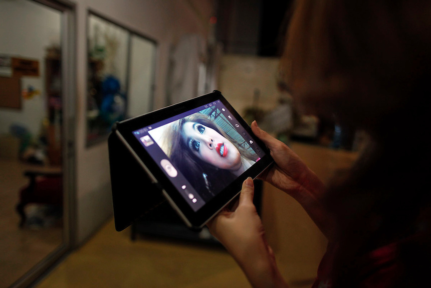 A transvestite performer checks her make-up using a tablet computer before going onto stage at the Tiffany's show in Pattaya late February 10, 2012. Originating as a one man show performed for friends on New Yearีs eve in 1974 in Pattaya, 150 km (90 miles) east of Bangkok Tiffany show became world famous transvestite cabaret with dozens of artists performing every night. Pattaya, a magnet for foreign tourists seeking sun, sea, watersports and racy nightlife, was a sleepy beach town until the 1970s and started to swell during the Vietnam War when U.S. troops, sailors and airmen flocked there for rest and relaxation.  Picture taken February 10, 2012. REUTERS/Damir Sagolj (THAILAND)