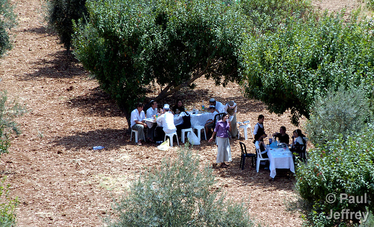 Israeli settlers have a Sabbath picnic in an olive grove belonging to Palestinian farmers in Hebron. Some 400 Israeli settlers, protected by 5,000 Israeli soldiers, have used intimidation and violence to drive Palestinian shopkeepers from the center of the ancient city of Hebron, in the southern part of the West Bank. Settlers have also chased Palestinians out of their own olive groves. Many claim that the ultimate goal of the settlers, who believe that they have a divine right to the land around Hebron, is to drive the Palestinians away permanently.