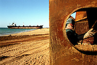 A worker at the Gaddani ship-breaking yard labours on a part of a ship. In the days when Gaddani was still in full operation it wasn't uncommon to find hundreds of ships here, all waiting to be broken up for scrap.