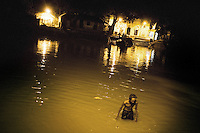 In the early pre-dawn morning, a man bathes in a dirty canal in Kolkata. Such places are breeding grounds for malaria mosquitoes...