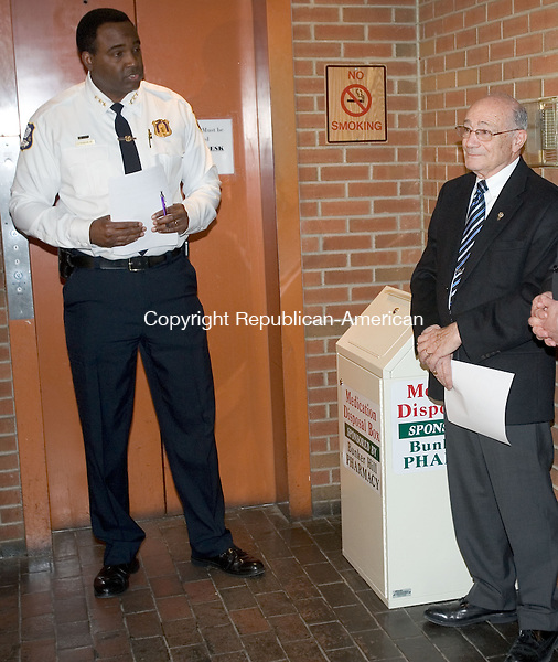 WATERBURY, CT. 05 April 2013-040813S08-Police Chief Vernon Riddick, left, announced the installation of a prescription drop box in the lobby of the police station in Waterbury Monday. The prescription drop box was donated by Mr. William Summa, at right, the owner of the Bunker Hill Pharmacy which is located in Waterbury. Members of the public will now be able to anonymously turn in unwanted, unused or expired prescription drugs before they fall into the wrong hands (children, criminals, or substance abusers) or damage our environment through improper disposal..Steven Valenti Republican-American