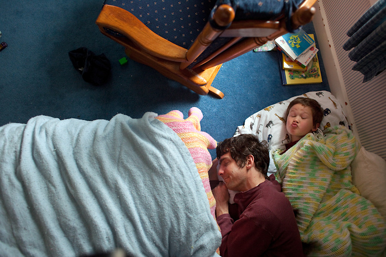 "As our son got older and less likely to sleep in the afternoon, ""naptime"" became ""rest time"", and then, optimistically, ""quiet time."" There were still days when he really needed to sleep but wouldn't. One afternoon my husband said he was going to lie down with him. I came in later, thinking it would be a sweet photograph, but found that my son, then four, had the last laugh once again. The blankets are on the floor because my husband tried to create a cozy nook that would be more appealing to our son than bed."