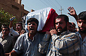 Iraqi men carry a flag draped coffin bearing the body of assasinated Iraqi Governing Council member Aquila al-Hashimi during her September 26, 2003 funeral in Baghdad, Iraq. Al-Hashimi, one of three women on the Governing Council and a Shiite Muslim, was gunned down on her way to work September 20, 2003.