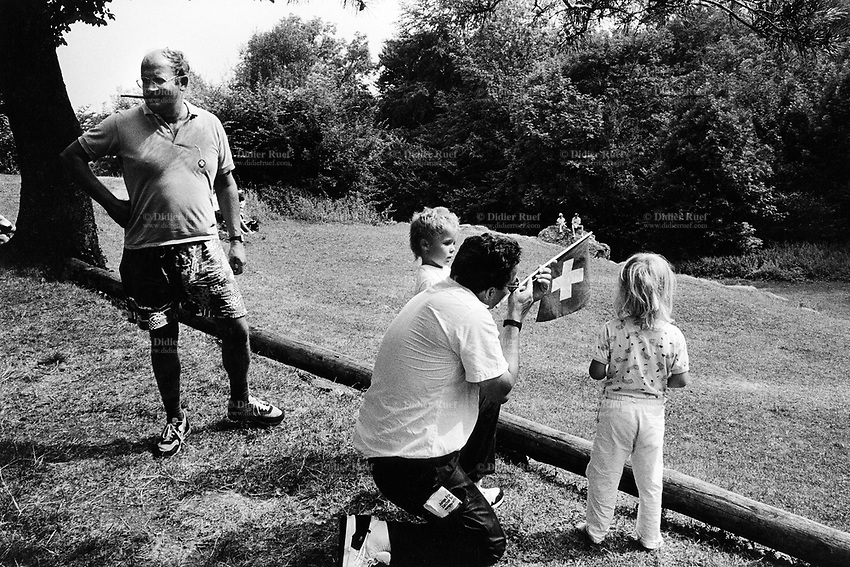 Switzerland. Canton Uri. Rütli feld. 1 August 1990. Swiss national holiday. Public holiday. A father teaches his children (a boy and a girl) how to use a swiss flag as a rifle. Rütli is the birthplace of the Swiss Confederation. © 1990 Didier Ruef