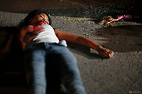 """A 17 year old girl lays dead next to her doll after she and her friend were killed by unknown motorcycle riding gunmen in an alley in Manila, Philippines early October 26, 2016. According to the police, a sign on a cardboard reading """"Tulak ka, hayop ka"""", which translates to """"You are a (drug) pusher, you are an animal"""" was found with the the body of girl's killed friend.   REUTERS/Damir Sagolj"""
