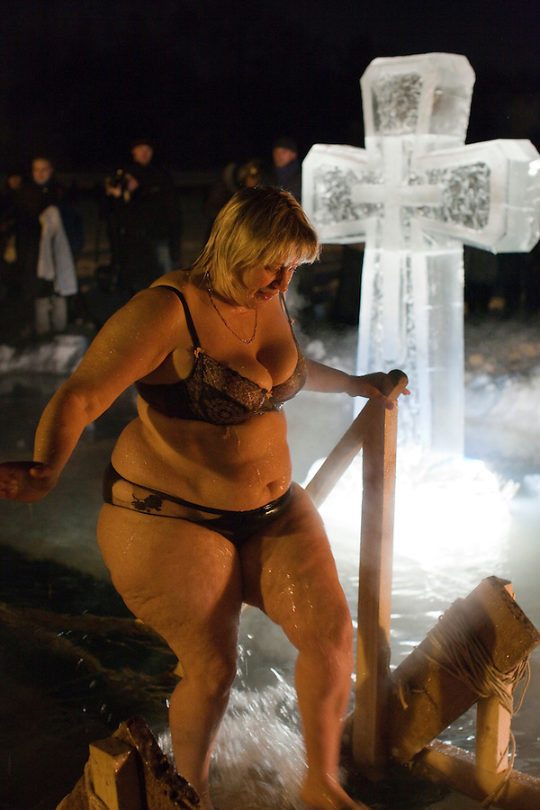 Moscow, Russia, 19/01/2011..A woman emerges from the water as Orthodox Christian believers celebrate Epiphany at a lake in eastern Moscow. Priests blessed the waters and followers baptised themselves by total immersion in the freezing lake in temperatures of minus 15C.