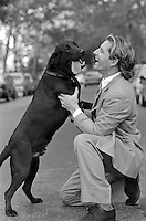 man in a suit kneeling down to play with a puppy