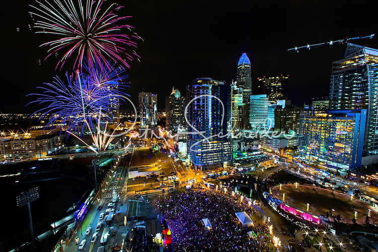 Charlotte Skyline Photography - Fireworks explode against the backdrop of the Charlotte North Carolina skyline, as thousands of people gathered at Romare Bearden Park on New Year's Eve to bring in 2017. CLT New Year's Eve celebration.<br /> <br /> Charlotte Photographer - PatrickSchneiderPhoto.com