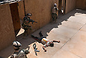 "17th Iraqi Division soldiers pass over a neutralized ""insurgent""  after simulating shooting him during training exercises August 30, 2010 at the Joint Security Station (JSS) Deason in Mahmoudiyah, Iraq."