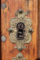 Keyhole and lock with detailed metalwork, on the door of the main entrance to the Joanina Library, or Biblioteca Joanina, a Baroque library built 1717-28 by Gaspar Ferreira, part of the University of Coimbra General Library, in Coimbra, Portugal. The Casa da Livraria was built during the reign of King John V or Joao V, and consists of the Green Room, Red Room and Black Room, with 250,000 books dating from the 16th - 18th centuries. The library is part of the Faculty of Law and the University is housed in the buildings of the Royal Palace of Coimbra. The building is classified as a national monument and UNESCO World Heritage Site. Picture by Manuel Cohen