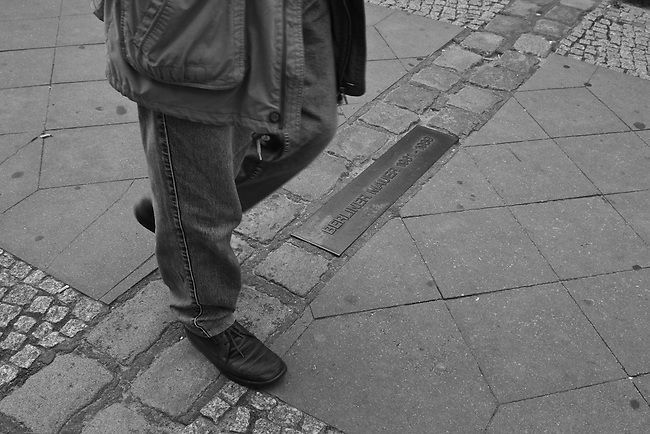 A double set of paving stones and a bronze plaque mark where the Berlin Wall divided the city from 1961 to 1989. Berlin, Germany. Aug. 1, 2007.