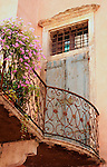 Looking up at a blue wooden door of a small balconywith an iron railing and pink flowers in Verona, Italy.