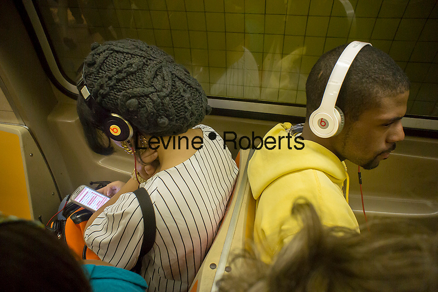 Subway riders wear their Beats by Dr. Dre headphones while riding on Saturday, September 28, 2013. The private equity Carlyle Group rcenlty invested $500 million in Beats Electronics.   (© Richard B. Levine)