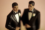 Non-traditional marriage ceremony with gay black men figurines on a wedding cake wearing tuxedos with sunset light.