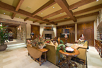 Mediterranean decore family room with beamed ceiling and beautiful built-in cabinets and rich furnishings