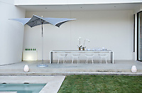 A long contemporary dining table and Bertoia chairs on the concrete terrace with a silver parasol