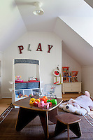The bright play room has a clever storage system that doubles as a toy market stall