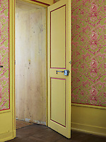 The yellow-painted door of this guest bedroom decorated in toile de Jouy opens on to an undecorated corridor