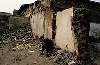 CHINA. Beijing. A man and sits amongst the ruins of an old hutong (tradtional homes) making way for new developments aimed at modernising the city for the 2008 Summer Olympics. 2005