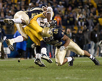 West Virginia University Running Back Steve Slaton is sandwiched by Pitt defenders Tommie Campbell (top) and Sam Bryant #46.  The WVU Mountaineers defeated the Pitt Panthers 45-27 on November 16, 2006 at Heinz Field, Pittsburgh, Pennsylvania.