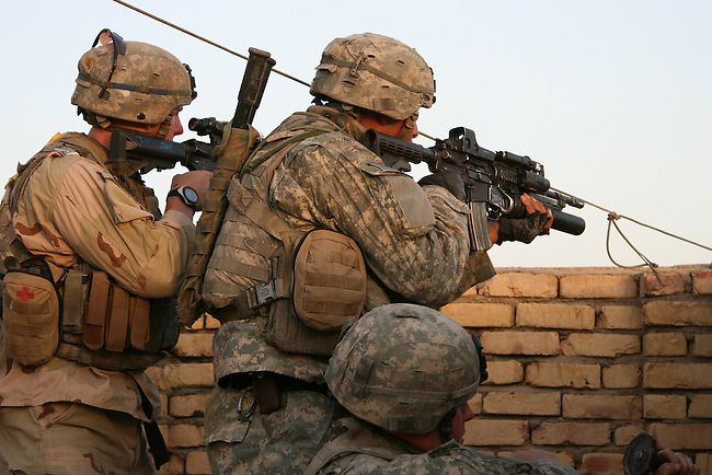 Two U.S. soldiers with Company C, 1st Battalion, 23rd Infantry Regiment return fire after insurgents begin shooting at them from a distant rooftop in Baqubah, Iraq. A third soldier tries to hammer out a firing slot in a brick wall. The action came a day after more than 10,000 U.S. and Iraqi soldiers moved into the city to clear it of insurgents. June 20, 2007. DREW BROWN/STARS AND STRIPES