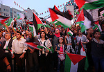 Palestinians wave their national flags as they watch a live-screening of president Mahmoud Abbas' speech followed by the raising of the Palestinian flag at the United Nations headquarters in New York, in the West Bank city of Nablus on September 30, 2015. Earlier in the week the UN General Assembly, by a two-thirds vote, adopted a resolution allowing the flags of Palestine and the Holy See ''both of which have non-member observer status'' to be hoisted alongside those of member states. Photo by Nedal Eshtayah