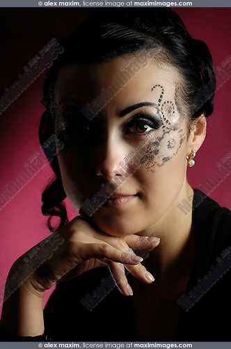 Stock photo of a Romantic expressive beautiful woman with a creative stencil pattern make-up and half face in shadow The woman has a Mona Lisa subtle smile Artistic emotional close-up portrait Isolated on dark red background
