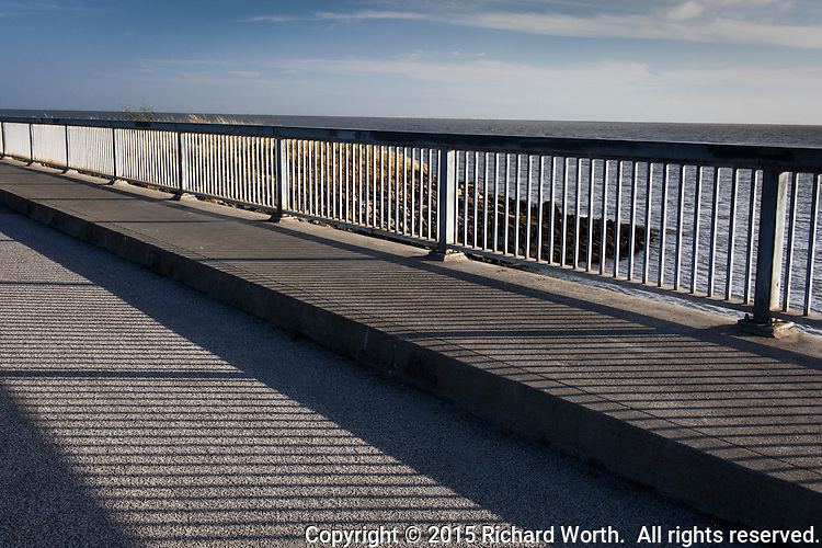 Late afternoon sun casts shadows on the walkway of a bridge along San Francisco Bay.