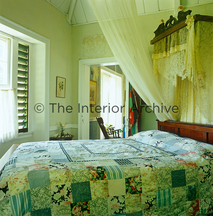 An antique mahogany bed covered with a rustic patchwork quilt is hung with mosquito netting and old lace from an ornate canopy