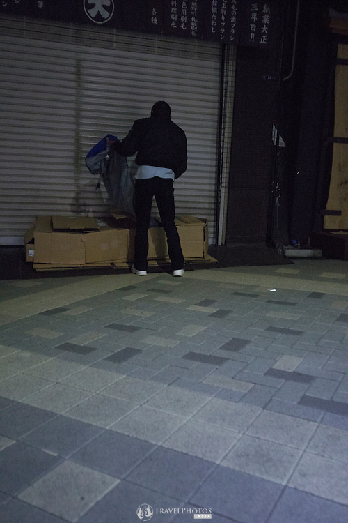 Homelessness in the tourist area of Asakusa, Tokyo. The homeless make box coccoons under the sheltered pedestrian paths in front of shuttered shops each night.