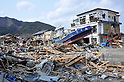 April 2nd, 2011, Ofunato, Japan - A fishing boat, apparently washed away by a tidal wave, rests in front of a damaged house in Ofunato City, Iwate Prefecture, on April 2, 2011, three weeks after this northeastern Japanese fishing port nestled deep inside an inlet was destroyed by a magnitude 9.0 earthquake and ensuing tsunami. (Photo by Natsuki Sakai/AFLO) [3615] -mis-...