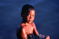 A young Palauan boy shimmering in the last light of the day holding on a large rock to help him diving one last time from the pier, an easy way for getting down without a weight belt.