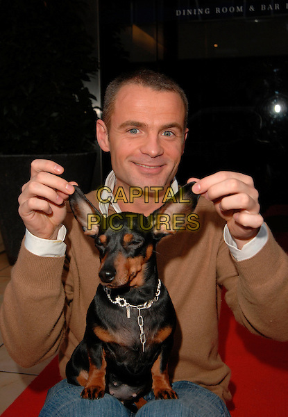JULIAN BENNETT.At the Andrex Puppy Red Nose Day Charity Lunch and Auction, The Clerkenwell, London, England, .February 26th 2007..half length dog pet funny holding ears.CAP/CAN.©Can Nguyen/Capital Pictures